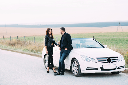 Sympathetic couple husband and wife spend time outside the city and stand by a white car. Zdjęcie Seryjne
