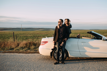 Sympathetic couple husband and wife spend time outside the city, sitting on a car hood.