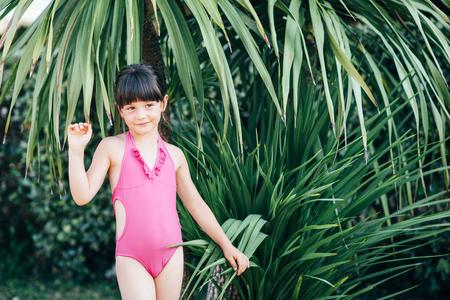 Una niña linda en un traje de baño rosa está pasando tiempo en la naturaleza en el verano. Foto de archivo