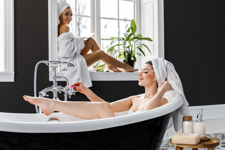 Cute young women dressed in white dressing gowns and towels on the head have fun in the bathroom. Leisure