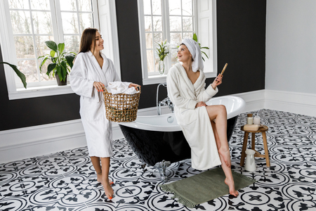 Cute young two women dressed in white dressing gowns and towels on the head have fun in the bathroom. Leisure
