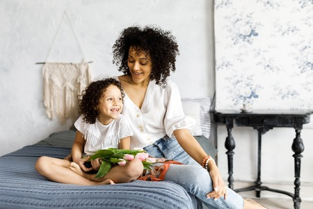 Mom and little cute curly girl sitting on bed with tulips in their hands.