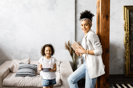 A cute mother and daughter talk and look at the tablet while standing in the living room. Standard-Bild