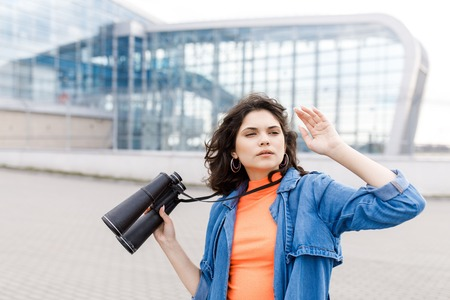 Young pretty girl looks away with a binocular in her hands. The young man travels