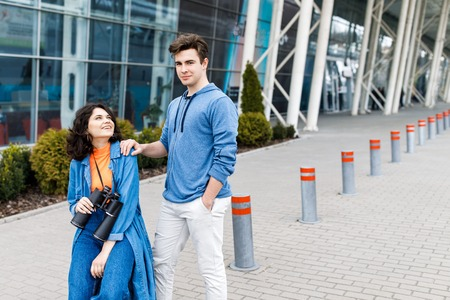 Young pretty couple - a boy and a girl walking around the city with a binocular in his hands. Young people travel.