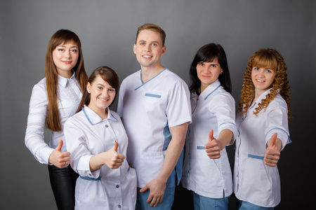 Portrait of doctors of otolaryngologists and nurses on an isolated grey background