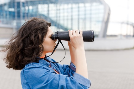 Young pretty girl looks away with a binocular in her hands
