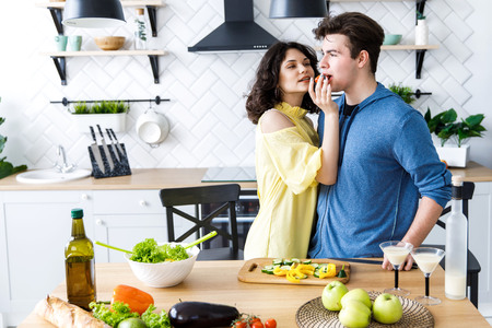 Young cute smiling couple cooking together at kitchen at home