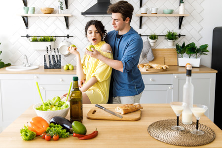 Young cute smiling couple cooking together at kitchen at home. A couple - a girl and a boy who spend time together for cooking.