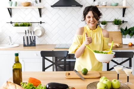 Young pretty woman cuts an avocado on a wooden salad board. Cooking. Stock Photo