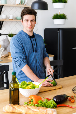 A young boy slicing an avocado on a wooden board for salad. Stock fotó