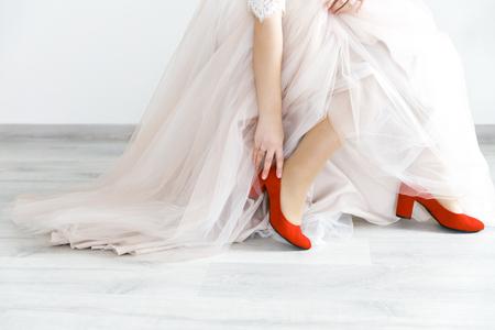 Panna młoda siedzi przed ceremonią ślubną w czerwonych eleganckich bucikach.
