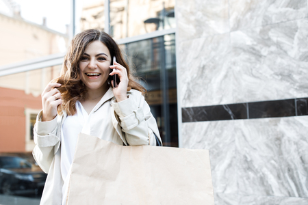 A young, sympathetic woman, not a thin-headed body building, walking around the city with a package for shopping, talking on the phone and having fun