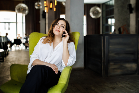 Beautiful smiling young woman dressed in dress sitting in chair at the cafe, talking on mobile phone Stock Photo