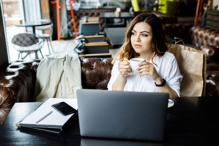 A young, sympathetic woman, not a thin-headed body building, sits in a cozy cafe, works on a computer and drinks coffee. Stock Photo