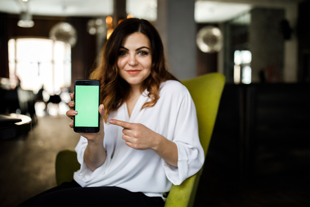 Happy beautiful young woman with long hair holding blank screen mobile phone and pointing finger