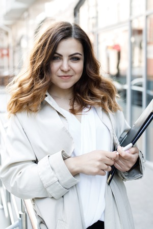 A young, sympathetic woman, not a thin-headed body building, holds a folder of paper in her hands. Happy young business woman with a folder at the office building in her hands