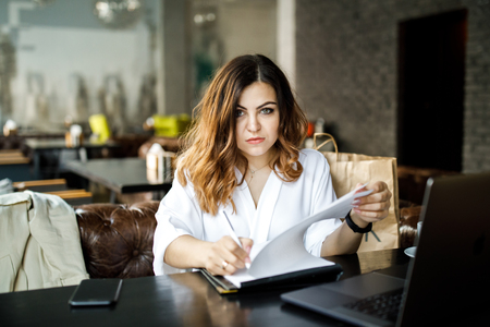 A young, sympathetic woman, not a thin-headed body building, sits in a cozy cafe, works at a computer, reviews documents. Business clothing style. Banco de Imagens