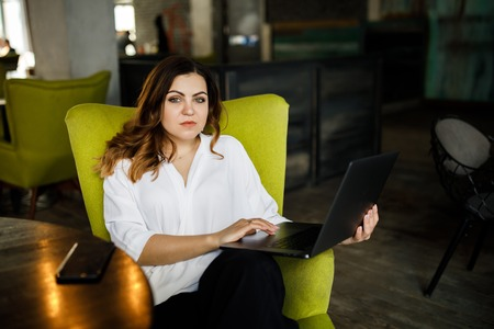 A young, sympathetic woman, not a thin-headed body building, sits in a cozy cafe and works for a laptop. Business clothing style.