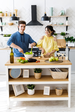 Beautiful couple in kitchen. Handsome man is preparing a salad while his girlfriend is cutting bread, both are smiling and have fun time
