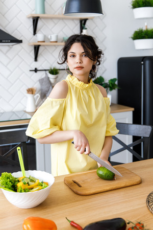 Young pretty woman cuts an avocado on a wooden salad board. Cooking. Фото со стока
