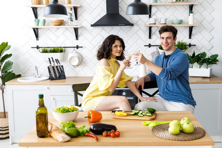 Young cute couple - a boy and a girl romantically spend time in the kitchen. A couple drinks alcohol and prepares a salad