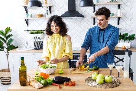 Young people are preparing a salad in a good kitchen Stock Photo