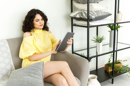Woman holding tablet, scrolling pages while sitting on the couch in the living room. 写真素材