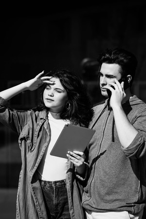 Young cute couple - a boy and a girl standing near a glass building. The guy speaks on the phone, and the girl holds a tablet in her hands