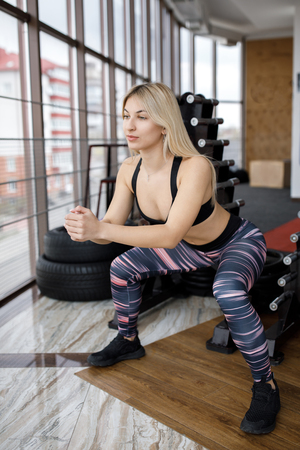 Beautiful young sportswoman standing and doing squats in gym Banco de Imagens - 124946824