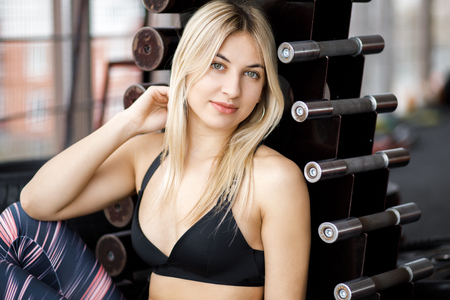 Attractive sportive girl sits on the floor in the gym next to the stand with dumbbells. Stock Photo