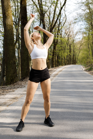 A young, pretty girl blonde is training before running outdoors