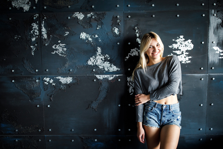 A young, sympathetic blonde is standing, dressed in a lingerie and denim shorts and smiles while looking at the camera. Studio