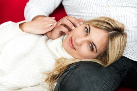 Young pretty couple of husband and wife spend time together, sitting on the couch and resting