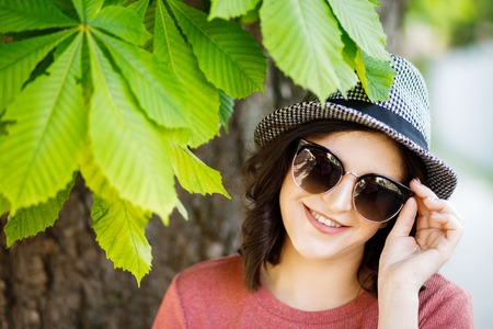 Young pretty brunette walking around the city on a sunny day, dressed in summer clothes, and a hat on her head. Imagens