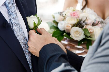 After the wedding ceremony, the groom is hugging a small rose on a jacket. Romantic vacation
