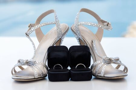 Silver wedding shoes and rings on the background of the sea and the island of Santorini