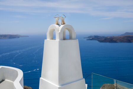 Silver wedding shoes on the background of the sea and the island of Santorini.