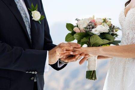 Marriage ceremony. The brides are exchanging wedding rings, the bride holds a wedding bouquet in her hand. Romantic vacation