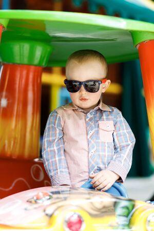 Little cute boy is having fun playing on a big toy car