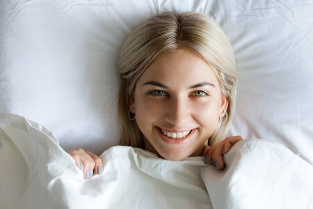 Happy morning. Portrait of a smiling pretty young blonde woman relaxing in white bed.
