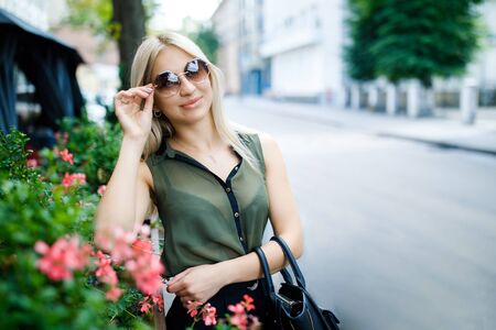 Young beautiful blonde girl standing in the middle of town in glasses. The girl is well dressed, business style. The girl is ready for a business meeting Reklamní fotografie