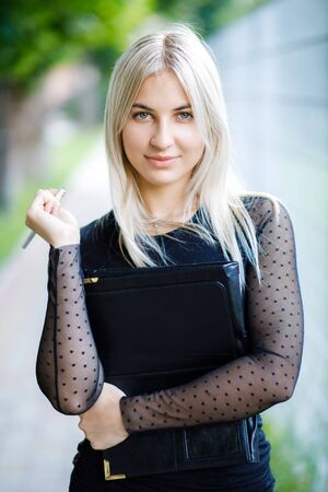 A young beautiful blonde girl wearing a classic black dress holds a folder of papers in her hands. Business clothing style. Reklamní fotografie