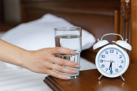 A white alarm clock and a glass of water are on a wooden bedside table. A woman stretches her hand to a glass of water Reklamní fotografie