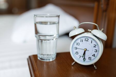 A white alarm clock and a glass of water are on a wooden bedside table.