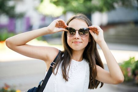 Fashion portrait pretty smiling girl in sunglasses enjoying outdoors in summer 写真素材