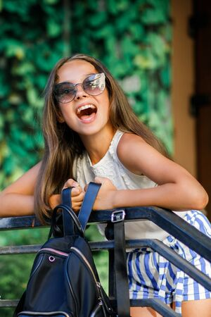 A cute, pretty teenage girl is having fun while on the street near the bike. Summer time