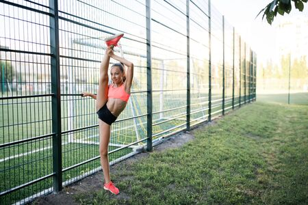 A young, sympathetic girl of slender body building, dressed in a form of sport, performs gymnastic exercises in the open air. Lifestyle Stock Photo