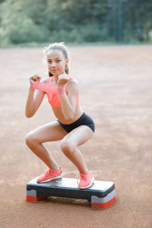 A young, pretty girl of slender body, dressed in a sports uniform, spends time on a sports ground and performs physical exercises. Lifestyle 版權商用圖片