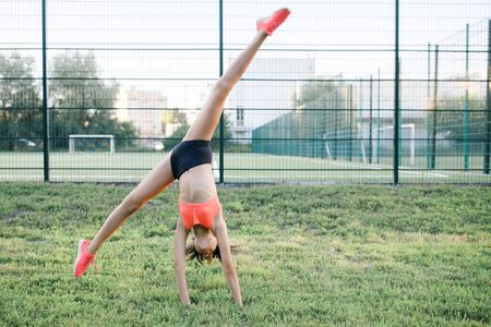 A young, sympathetic girl of slender body building, dressed in a form of sport, performs gymnastic exercises in the open air. Lifestyle